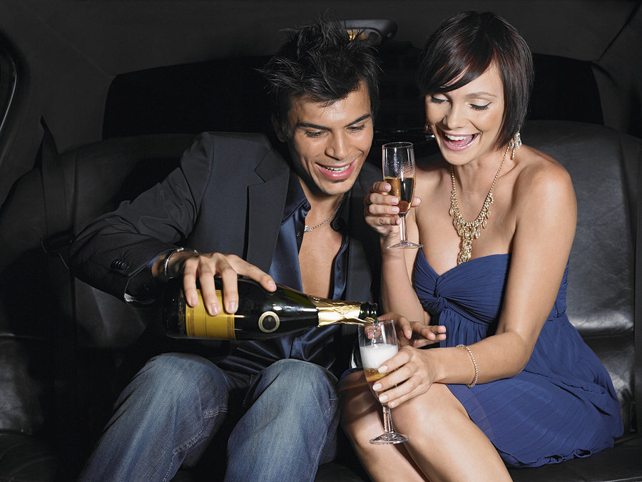 Happy young couple enjoying champagne in limousine